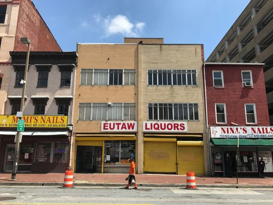 photograph of Eutaw Liquors, a storefront with bright yellow security roll up doors